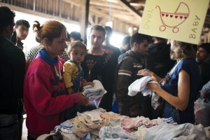A Syrian woman looks for clothes for her baby at the Mixer House in Belgrade, Serbia. CRS, working with Caritas, organized a distribution center providing hygiene kits containing soap, shampoo, sanitary napkins, toothbrushes, toothpaste, diapers, clothing for infants and other basic supplies to the thousands of refugees traveling to Germany. Catholic Relief Services (CRS) and Caritas are scaling up their humanitarian relief efforts to address these growing needs in Serbia, Macedonia and Greece. This is part of the Balkan Refugees - Migrants Response project. Photos by Kira Horvath for Catholic Relief Services